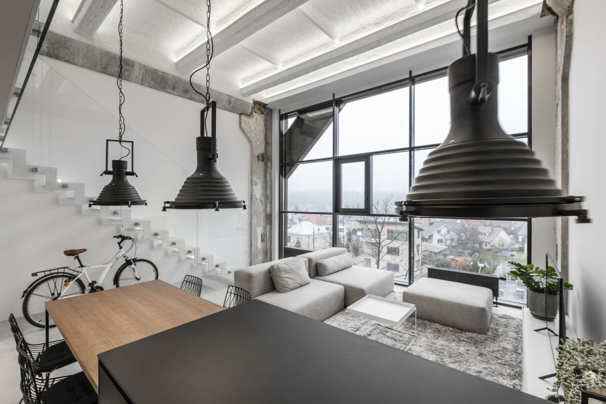 Three low-hanging industrial-style pendant lamps complement the black kitchen island and wooden table extension