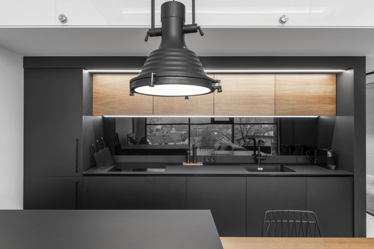 The open kitchen is almost completely black with the exception of the wooden accent surfaces