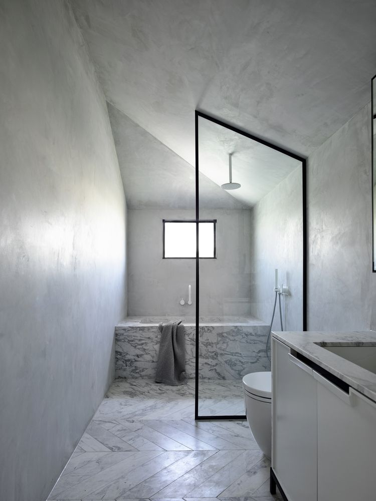 The clear glass divider allows the bathroom to look bright and airy in spite of its size and layout