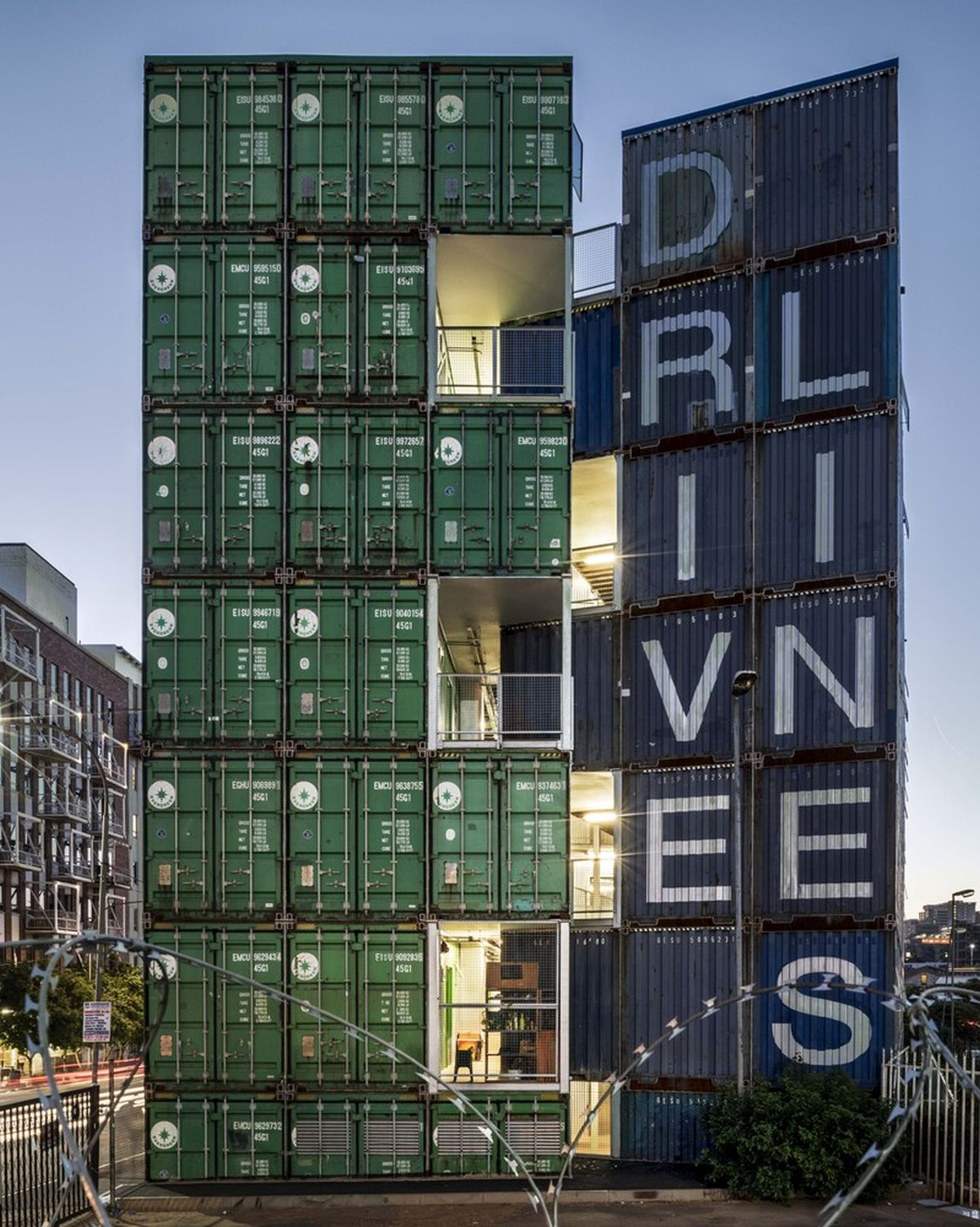 Green and blue reclaimed shipping containers are stacked forming six residential floors and a multi-purpose ground level