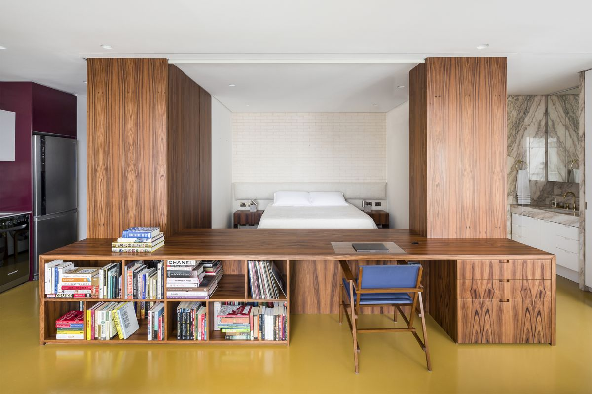 The bedroom is delineated by custom-built furniture units including two cabinets and a desk