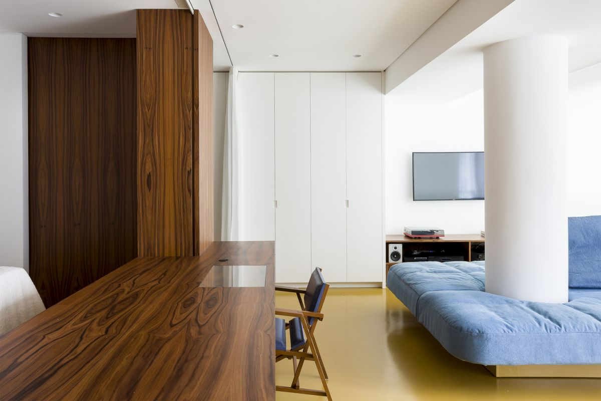 The apartment features yellow epoxy flooring which gives it a bold look while also visually connecting all the spaces