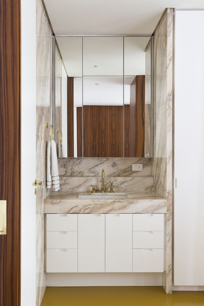The bathroom is small but elegant, featuring marble and mirrored surfaces