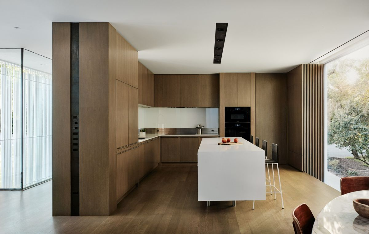 The indoor kitchen has an L-shaped plan with minimalist cabinetry and a white central island