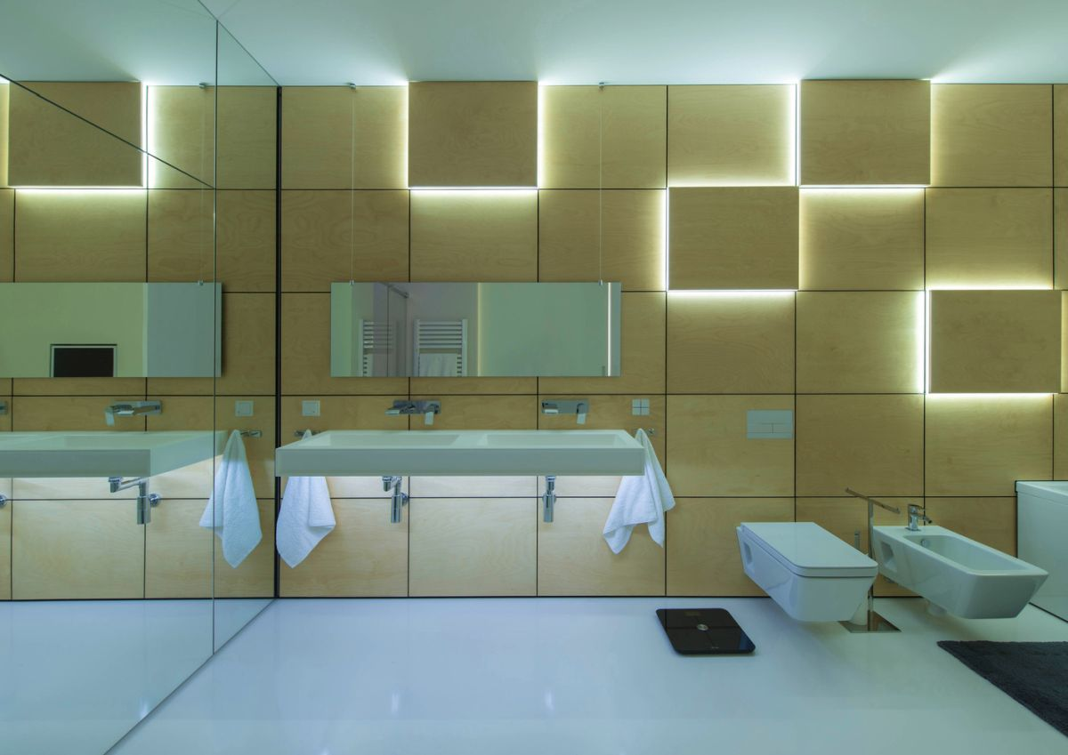 The mirror wall and accent lighting in the bathroom create an open and comfortable vibe