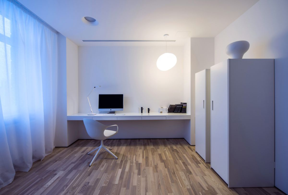 The studio home office featuring a wood floor which complements the white walls and adds