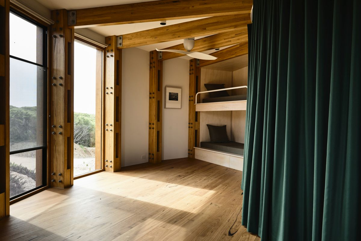 The upper floor acts as a large sleeping area with curtains instead of dividing walls