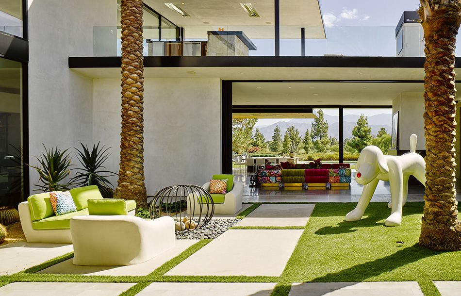The grass, furnishings and art blend into a cohesive patio space.