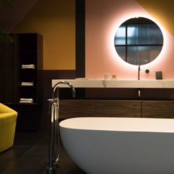 Baklit bathroom round mirror, cozy chair and freestanding tub