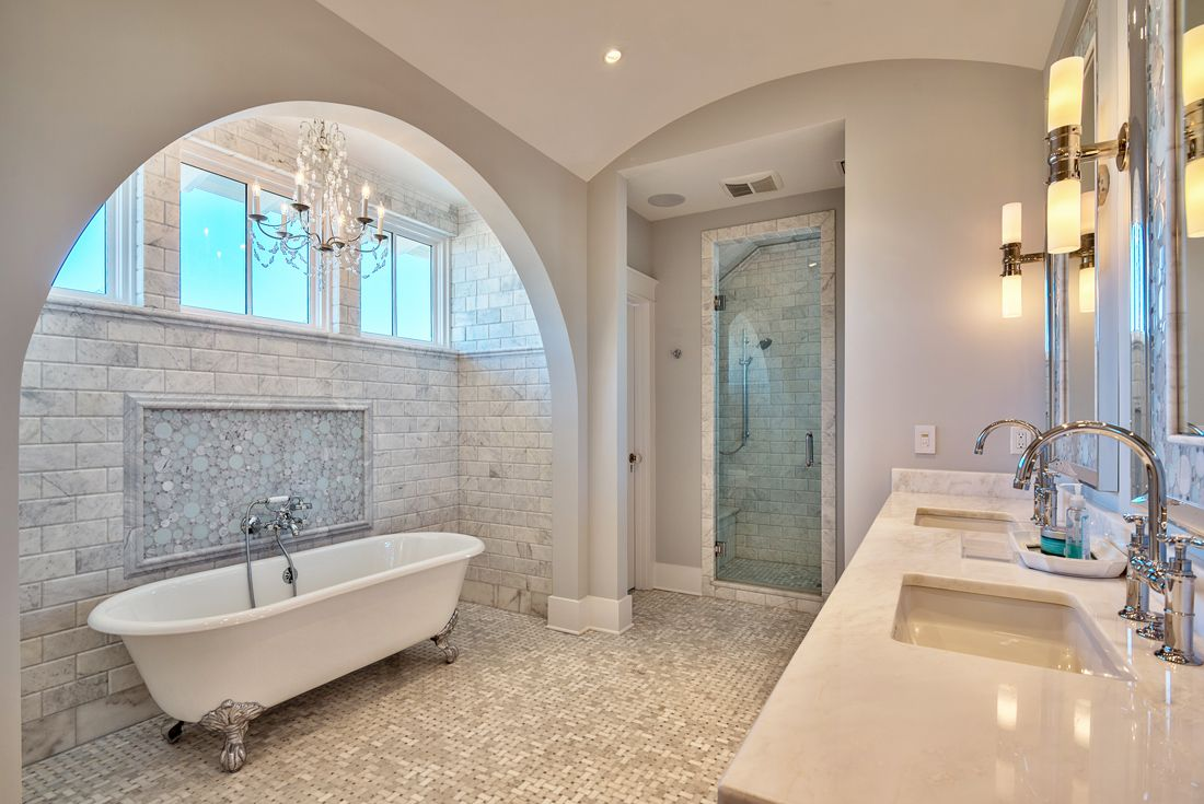 An arched wall frames the vintage clawfoot bathtub creating a sophisticated decor