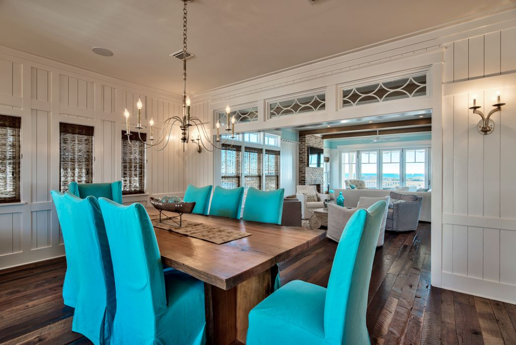 The dining area is very inviting thanks to the low-hanging chandelier and turquoise chairs