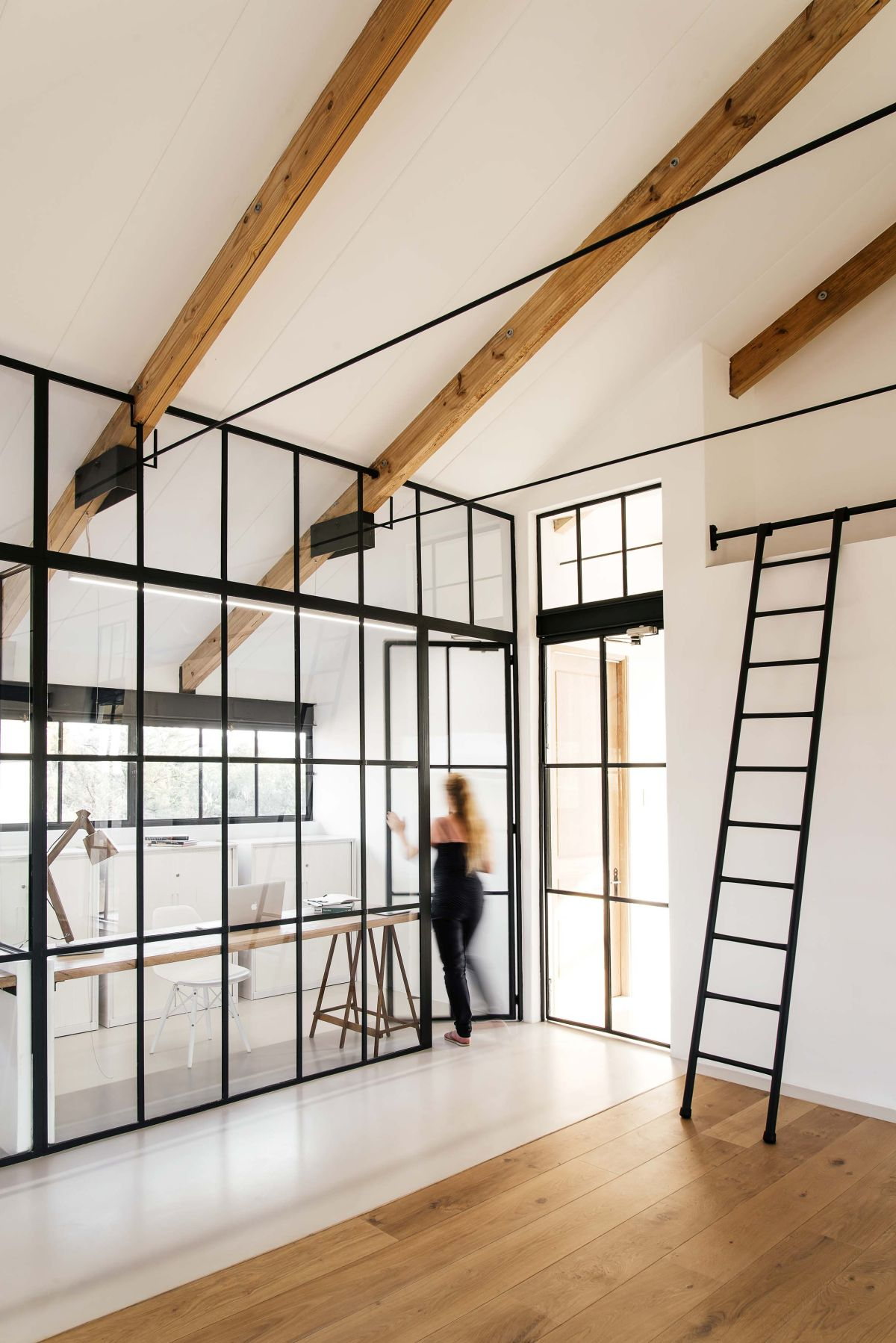 Glass walls and partitions matching the facade walls seamlessly connect various sections of the house