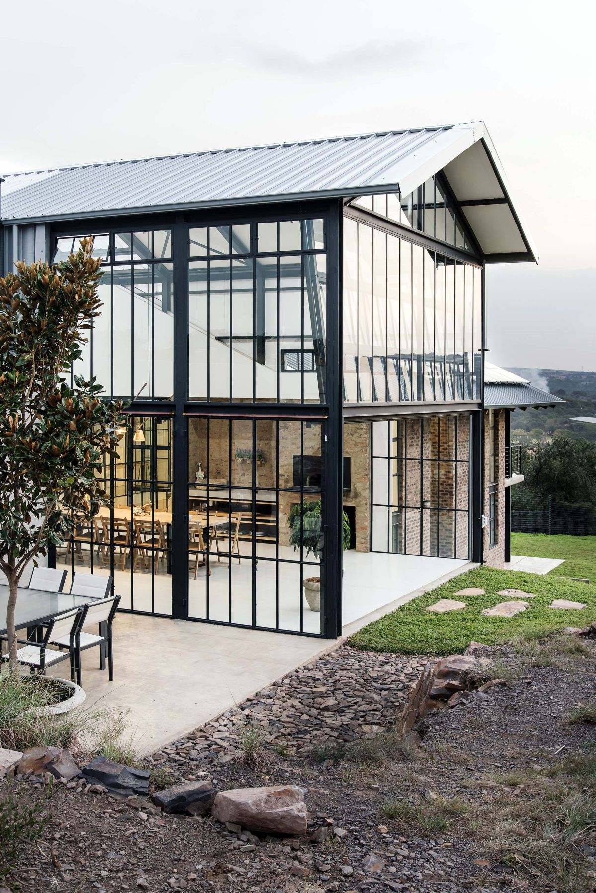 The double-height glass volume has a gabled roof and is filled with indoor plants which strengthens the connection between the house and the outdoors