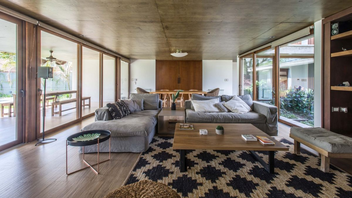 The living spaces are bright and open, featuring full-height windows and sliding glass doors