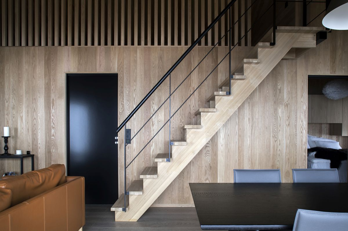 The staircase matches the wood paneling on the walls and blends in quite nicely