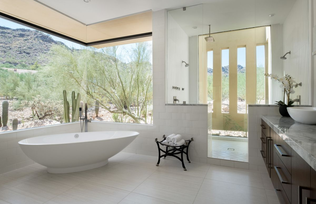 The master bathroom has a gorgeous view and features this amazing 90 degree window which makes everything look magical