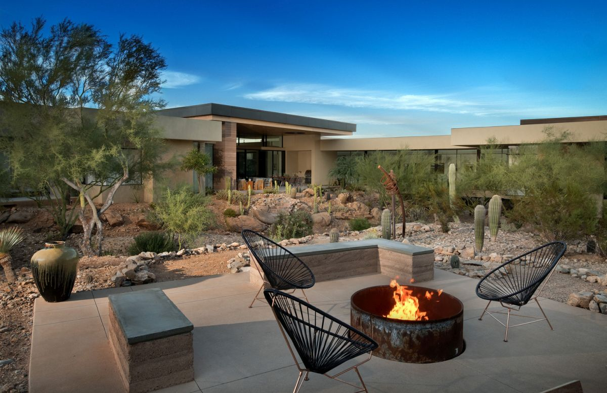 The comfort and elegance extend outdoors where there's this cozy seating with a fire pit at the center