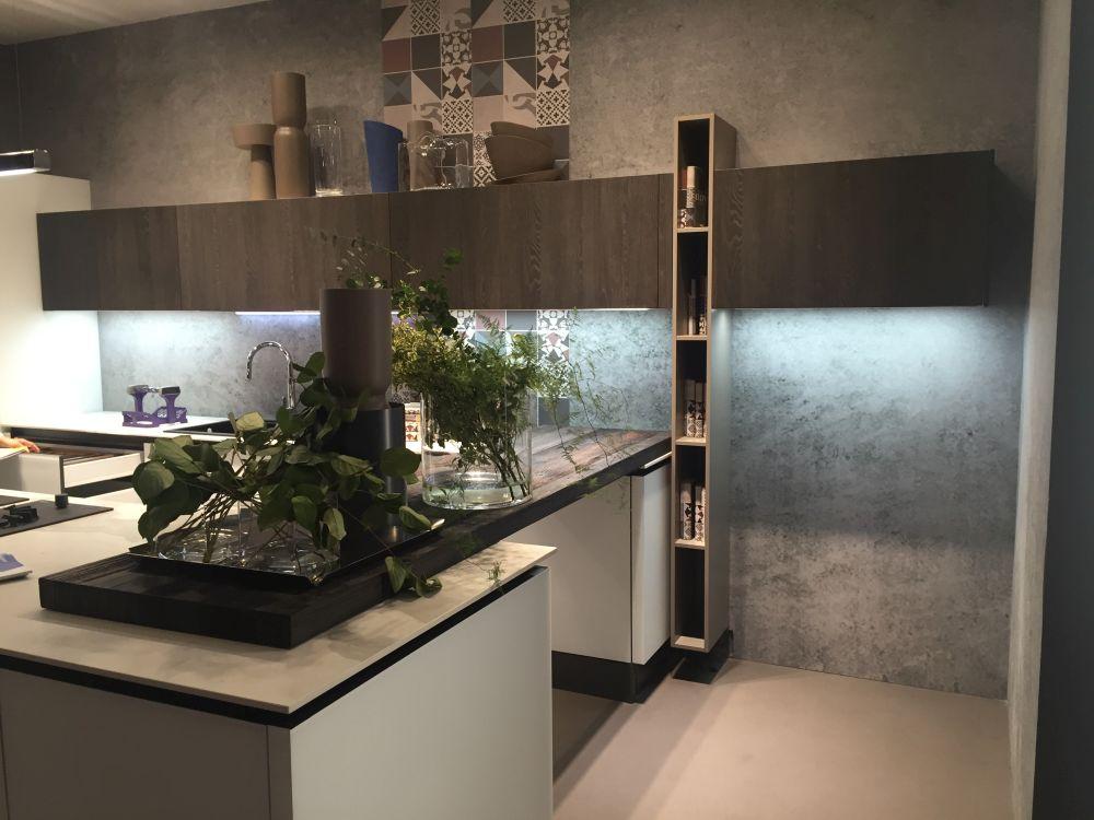 Ряд высоких и узких коробчатых полок пересекается с верхними шкафами и придает кухне геометрический вид