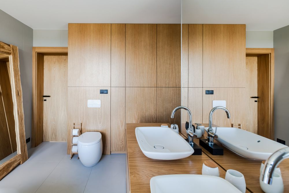 The double-sink bathroom vanity also acts as a space divider, helping to achieve a custom layout