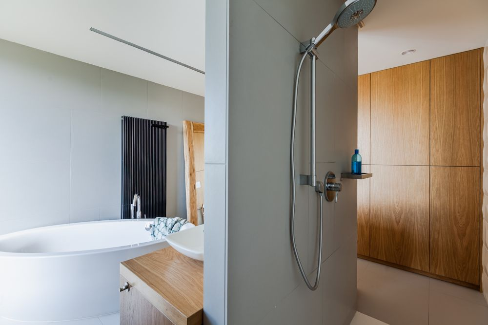 On the other side of the mirror wall there's a walk-in shower elegantly separated from the rest of the bathroom