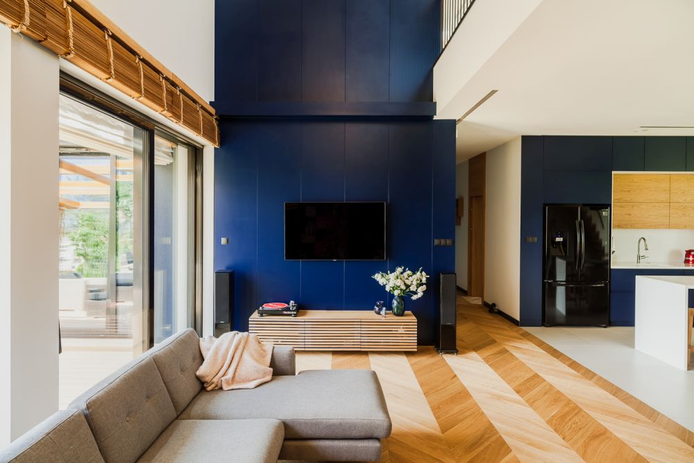 Dark blue surfaces are used in combination with wooden floors, furniture and white walls and neutral details