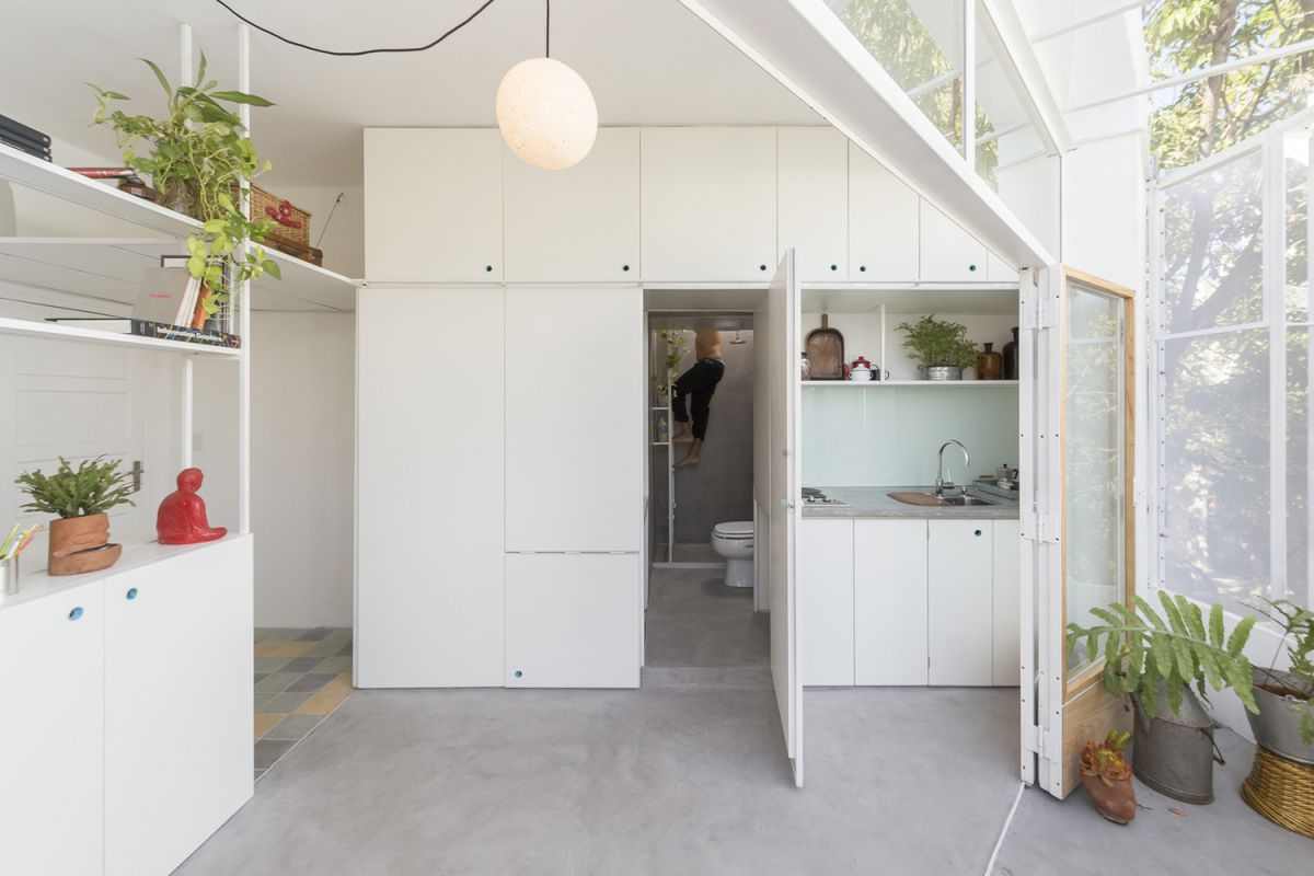 A small kitchen is incorporated into a furniture module with a door which conceals the entrance to the bathroom