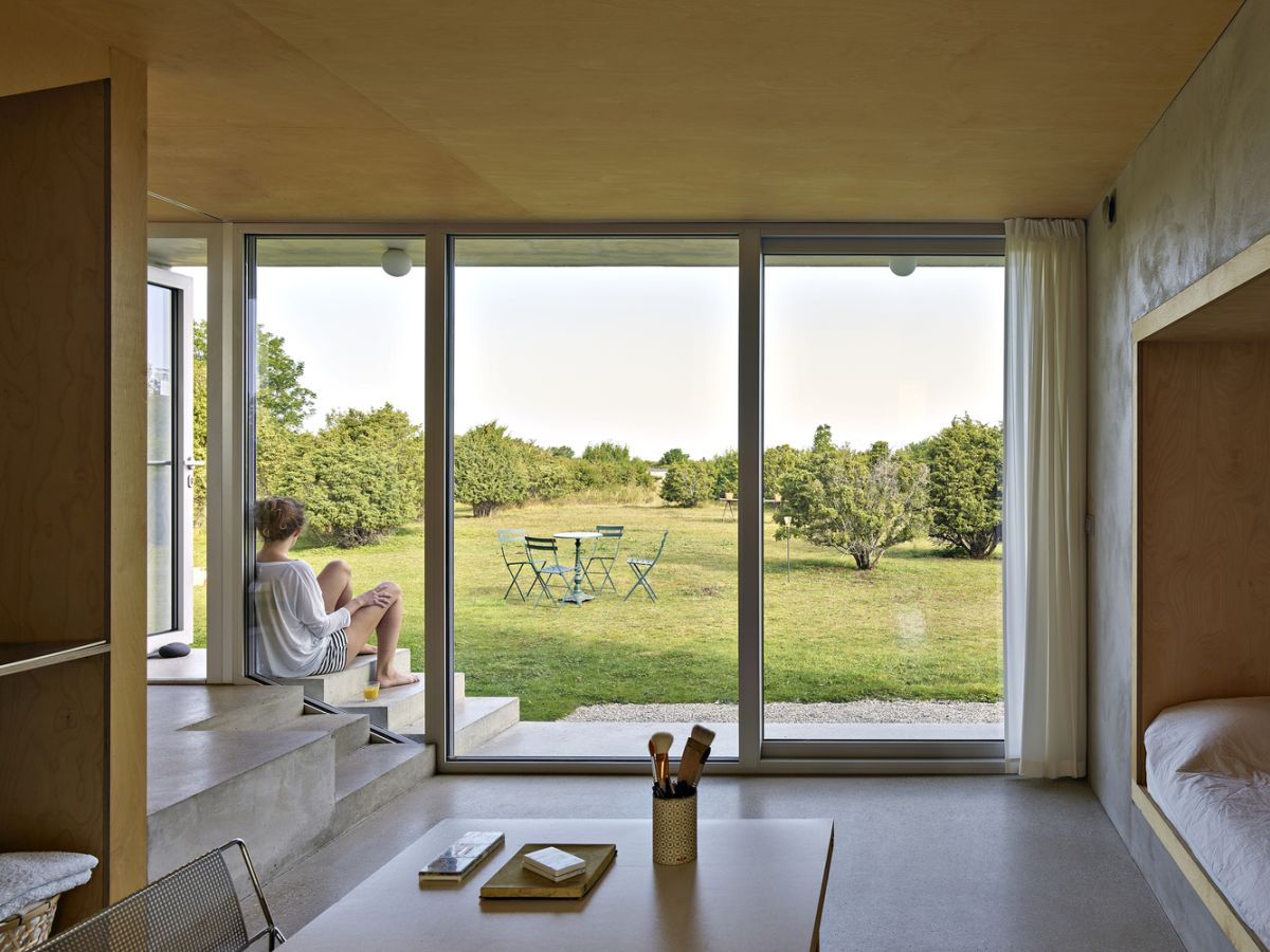 Sliding glass doors and large windows welcome views of the green surroundings inside the house