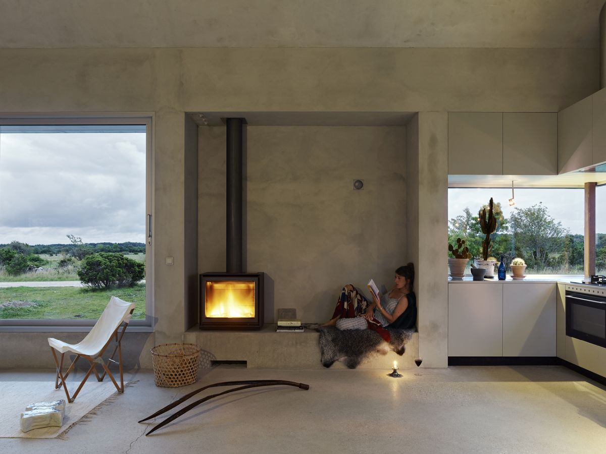 The grey walls and polished concrete floors are complemented by numerous cozy-looking details such as this fireplace