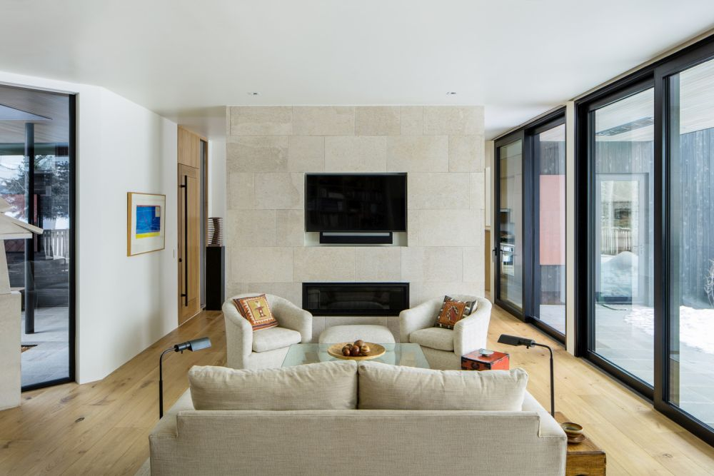 An elegant and welcoming family room is placed at the intersection of the two volumes, connecting them seamlessly