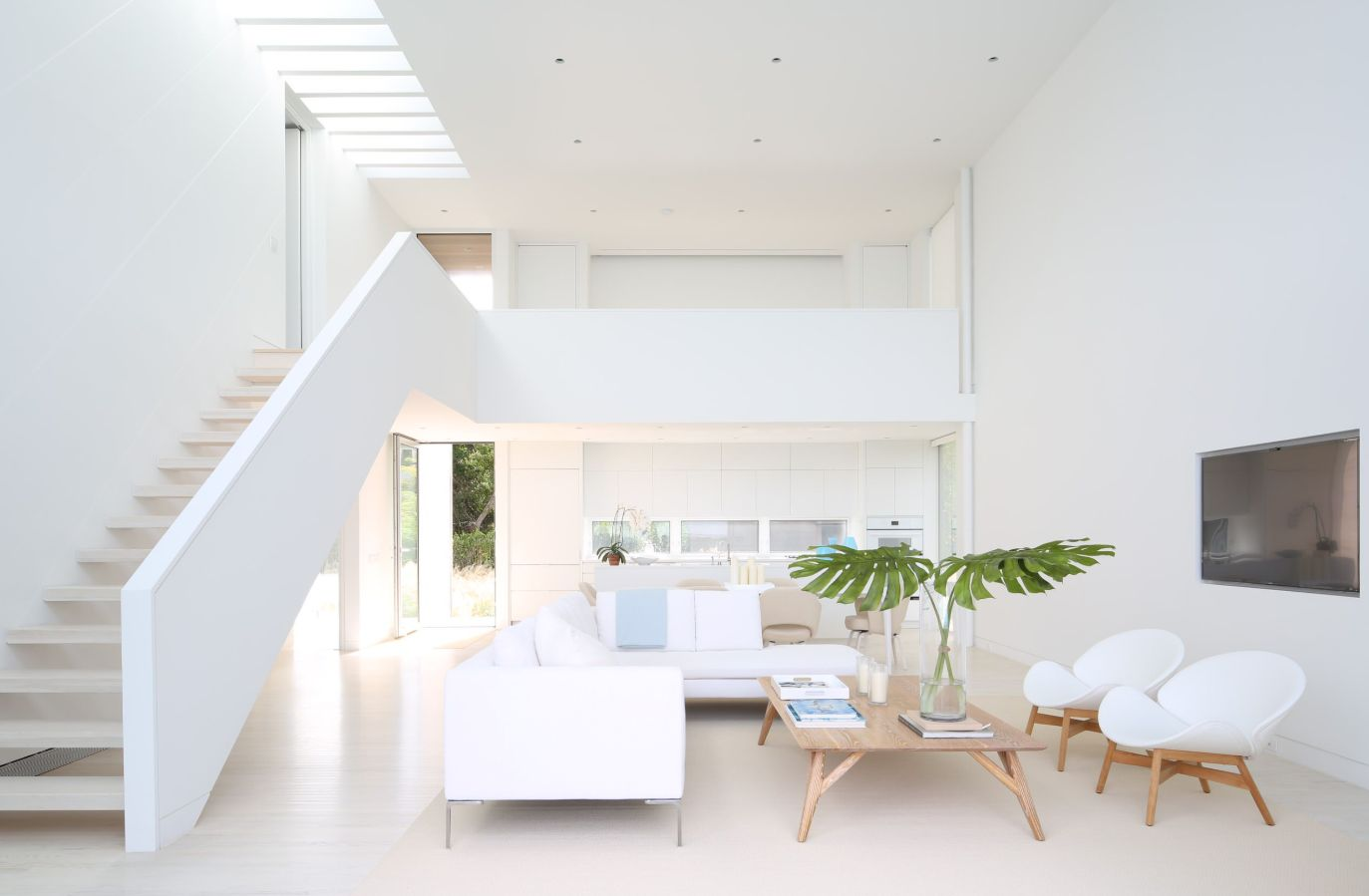 Pure white furniture and matching walls, floors and ceilings make this space seem bright despite the lack of windows