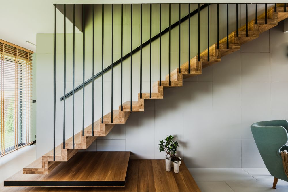 The minimalist staircase and its metal rod railing seem to be inspired by the house's facade design