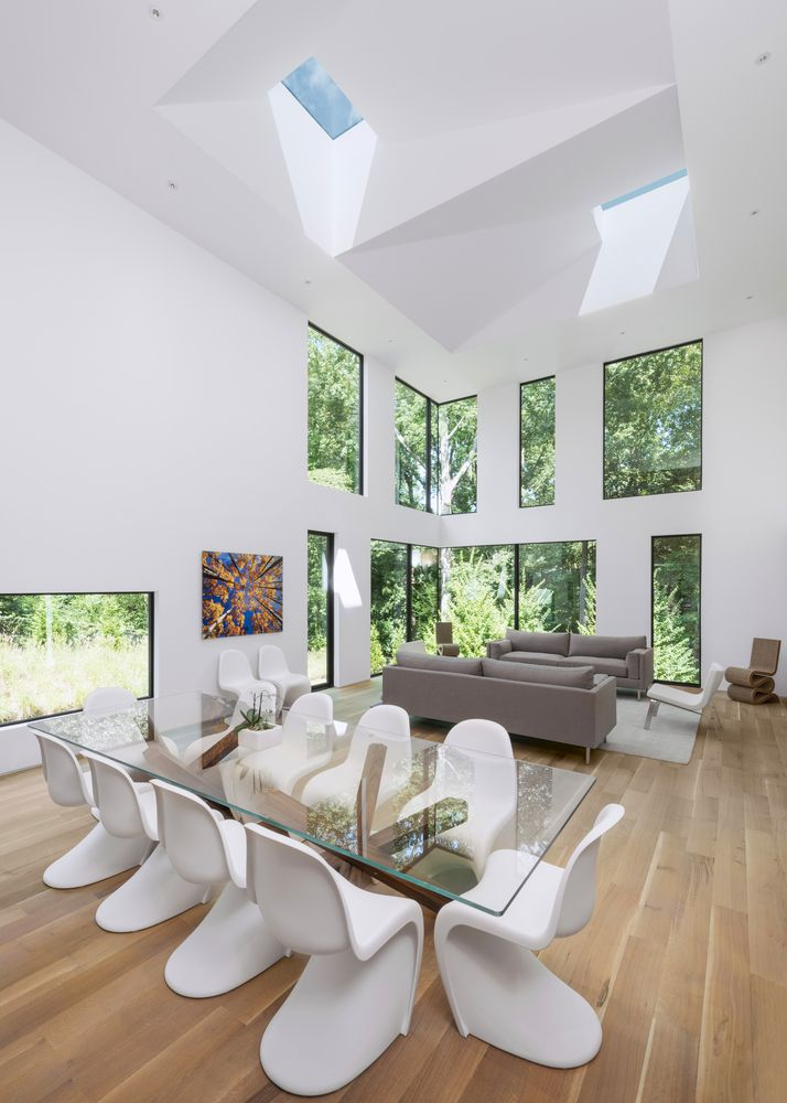 The double-height living area has multiple windows which bring the outdoors in as well as skylights