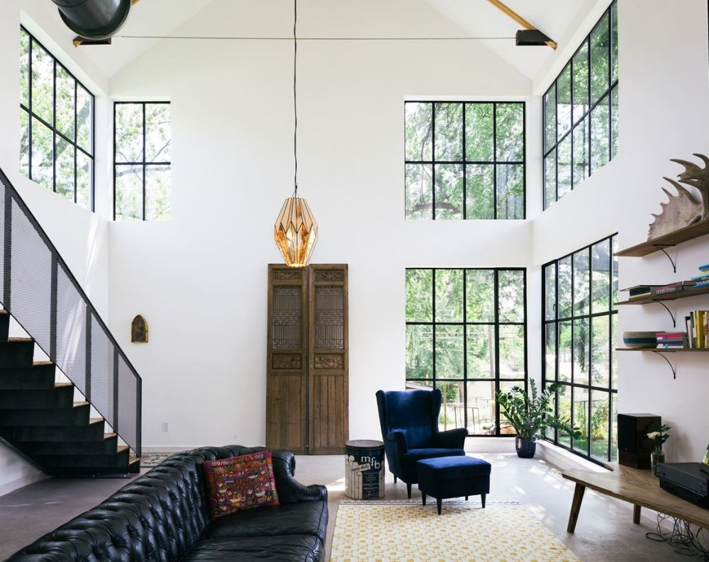 The living room is a double-height volume with large windows and an open floor plan