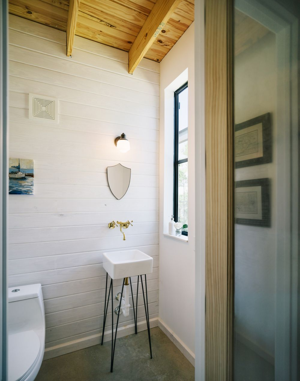 Although tiny, this bathroom doesn't look cluttered and that's all thanks to the interior design