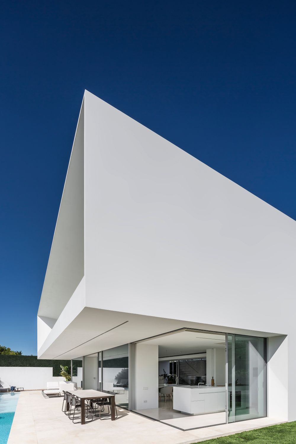 The house has a very clean and minimalistic aesthetic, featuring an all white exterior with large glazed surfaces