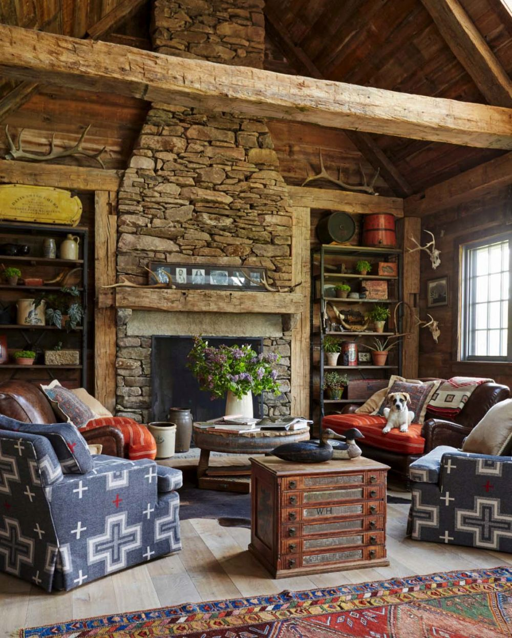The living room features a cozy seating area arranged in front of a large stone-clad fireplace