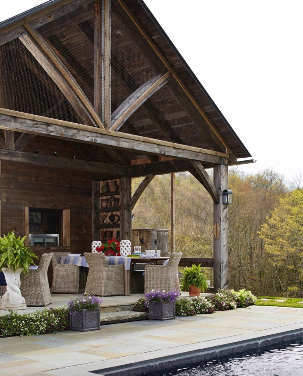 The house features a covered porch on one side, with an outdoor kitchen and comfortable furniture