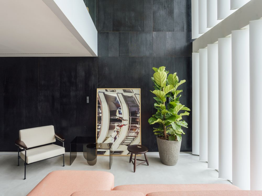 The palette of materials used throughout the apartment is limited to cement tiles, carbonized wood and concrete flooring