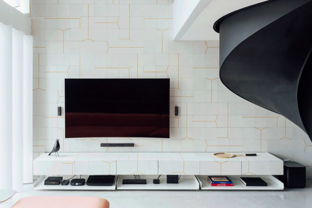The same type of tiles also covers the cabinet sitting below the TV