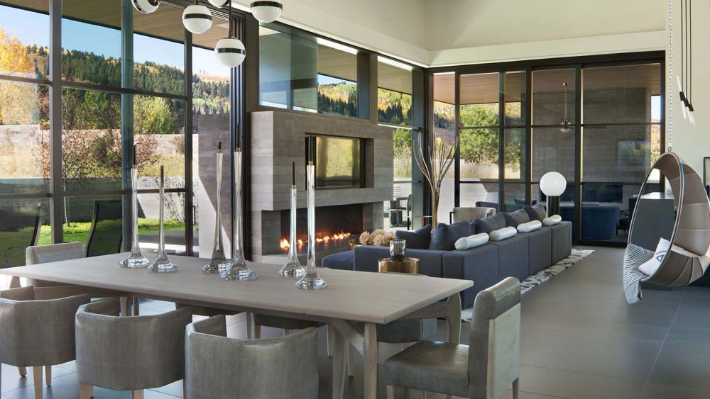 The living room is mostly frame by glass, with a fireplace section serving as a focal point