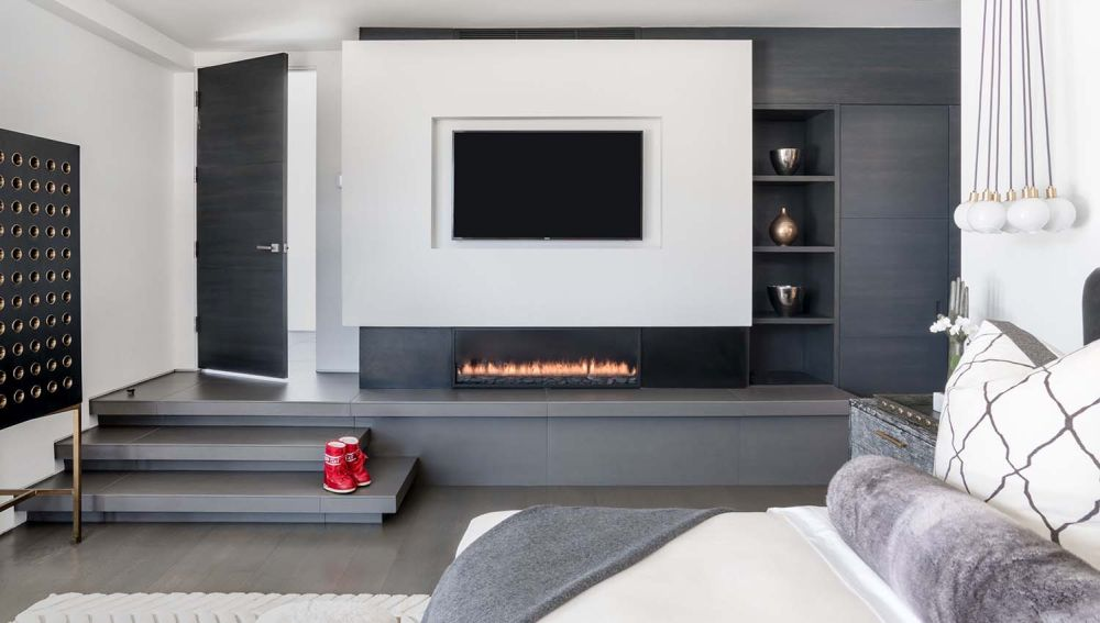 A third fireplace is built into this custom-built wall unit which marks the separation between the floor plans