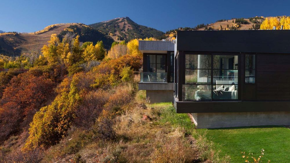 The house sits at the edge of the site, overlooking a steep ravine and a distant valley