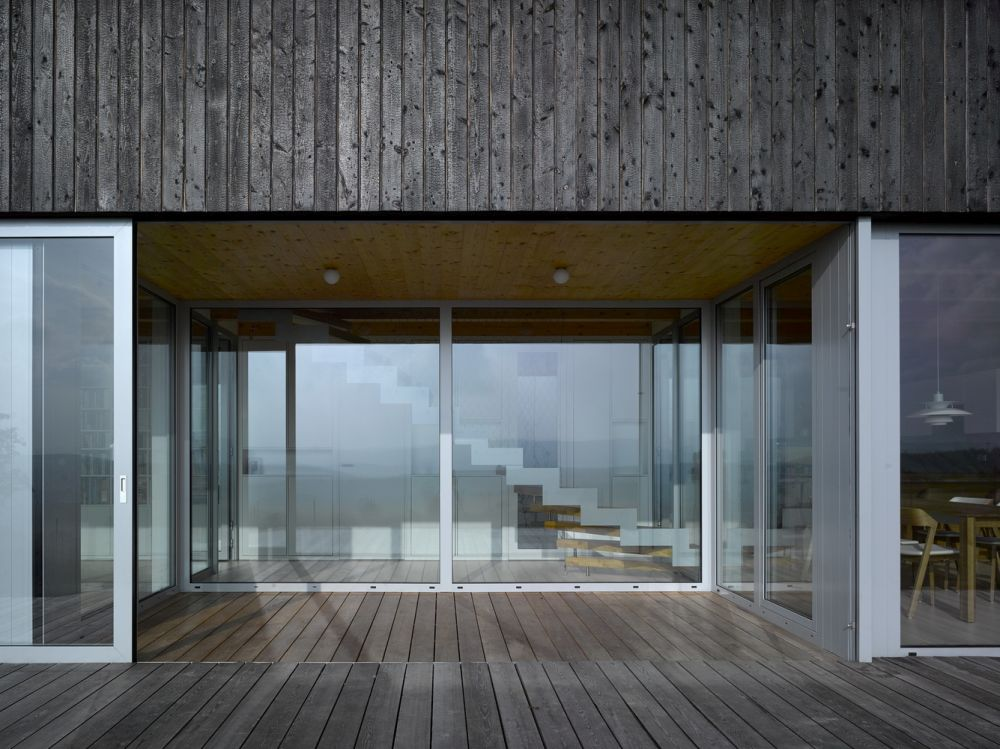 The exterior is clad in dark wooden planks which get their color from a natural treatment involving heat