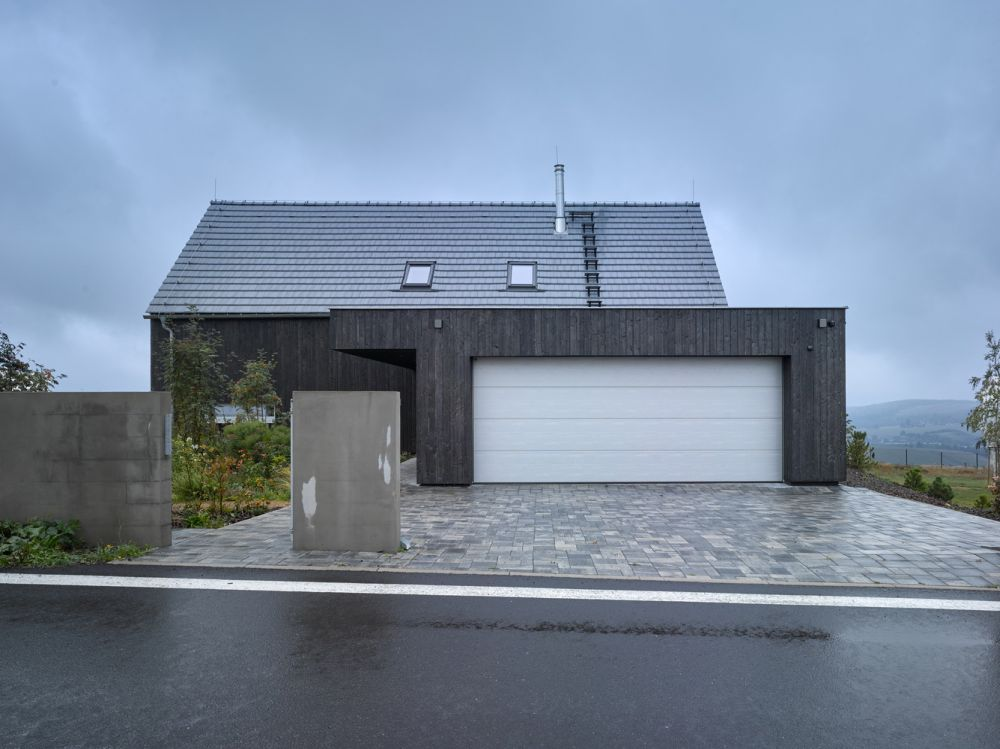 A two-car garage partially conceals almost half of the front facade
