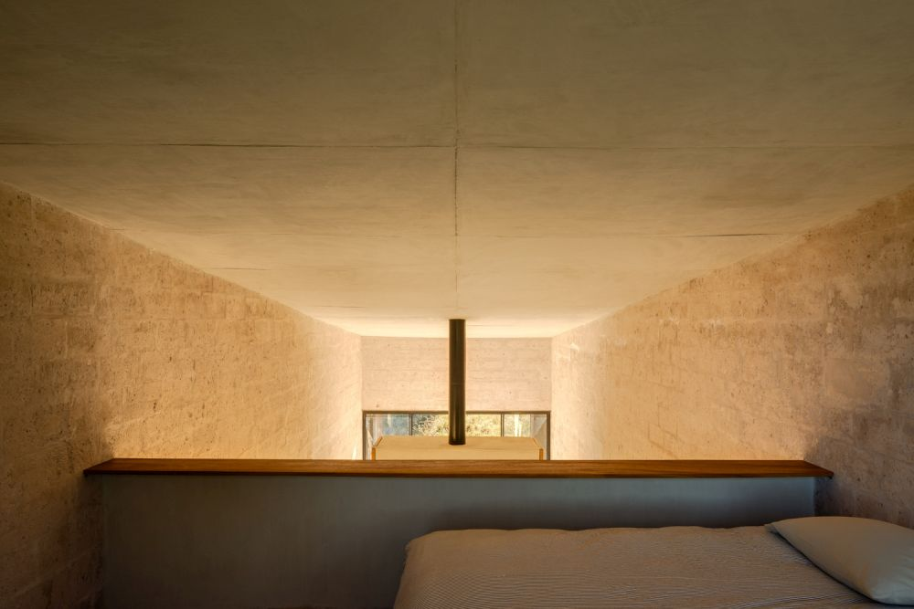 A loft area serves as a cozy sleeping nook and helps to keep the footprint of the house small