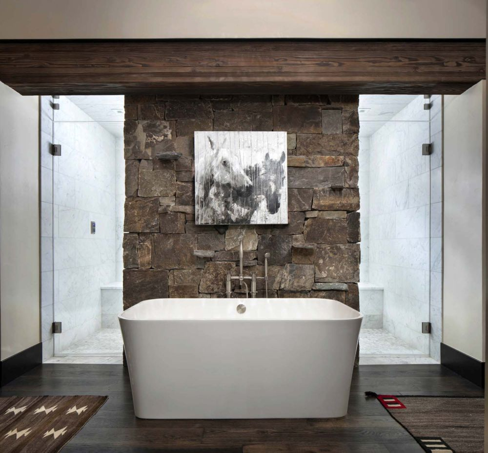 The master bathroom features a stone-clad accent wall and a walk-in shower with two entrances
