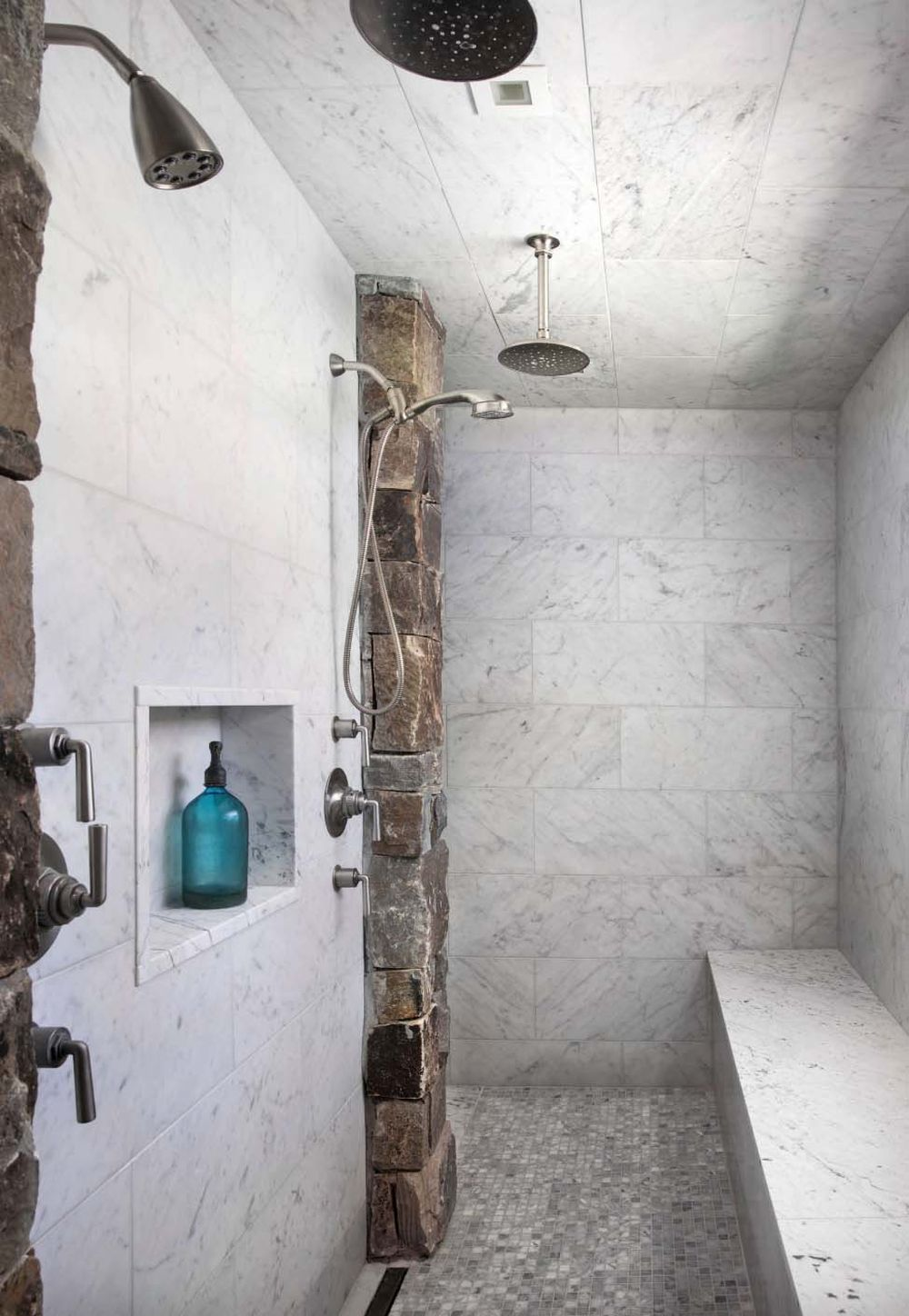The combination of natural stone and marble tiles gives the walk-in shower a unique character