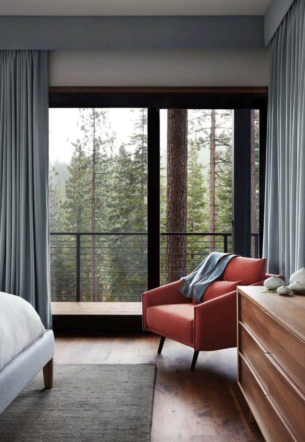The armchair in the corner of the bedroom overlooks the valley and gives the room a sense of completion