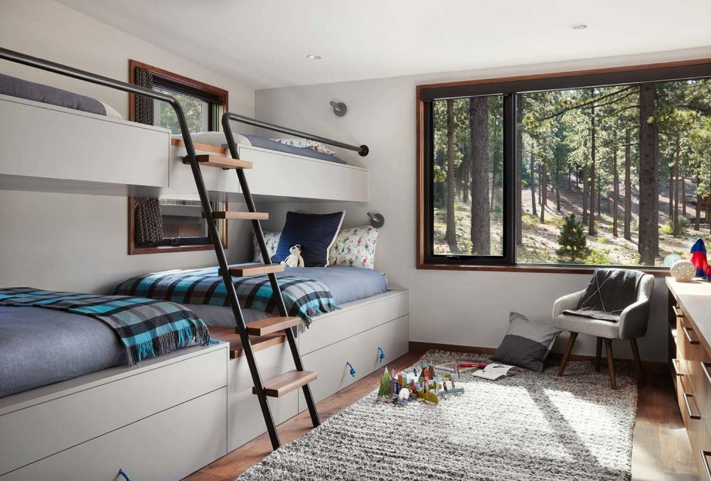 Bunk beds with built-in storage systems at the bottom maximize the floor space in this shared bedroom