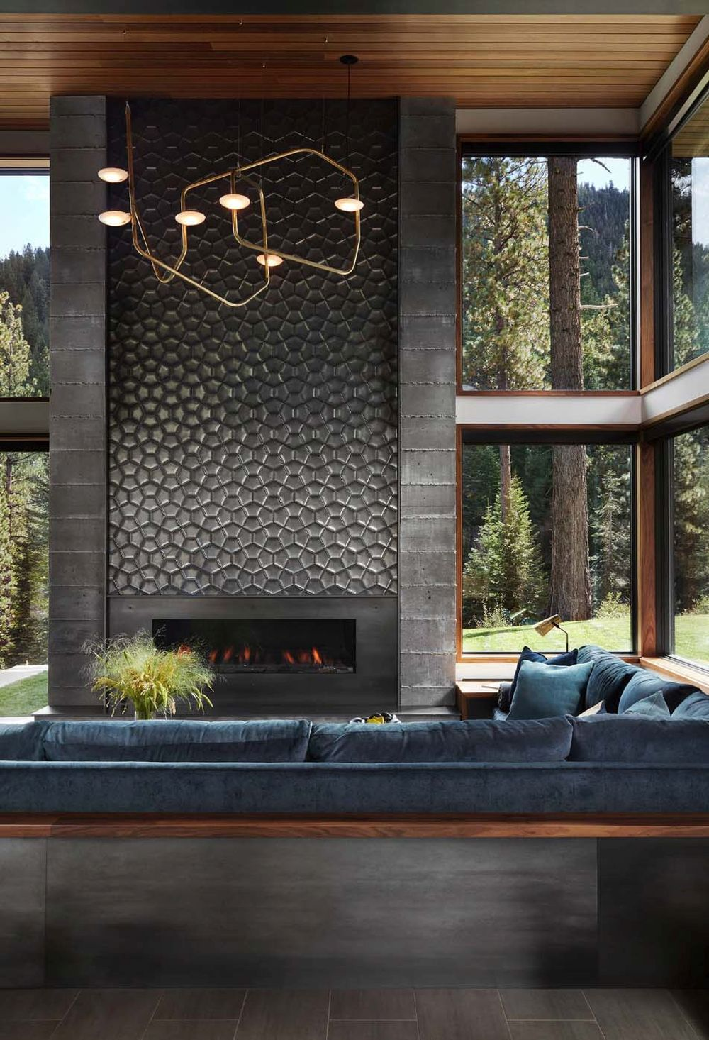 The fireplace wall is covered in little hexagon-shaped stones and this gives an amazing and eye-catching look